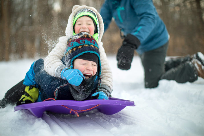location photography, lifestyle photography, winter lifestyle photography, advertising photography, kids sledding, children sledding, laughing kids, laughing children, children in snow, kids in snow, brothers playing, brothers laughing, children and father, kids with father